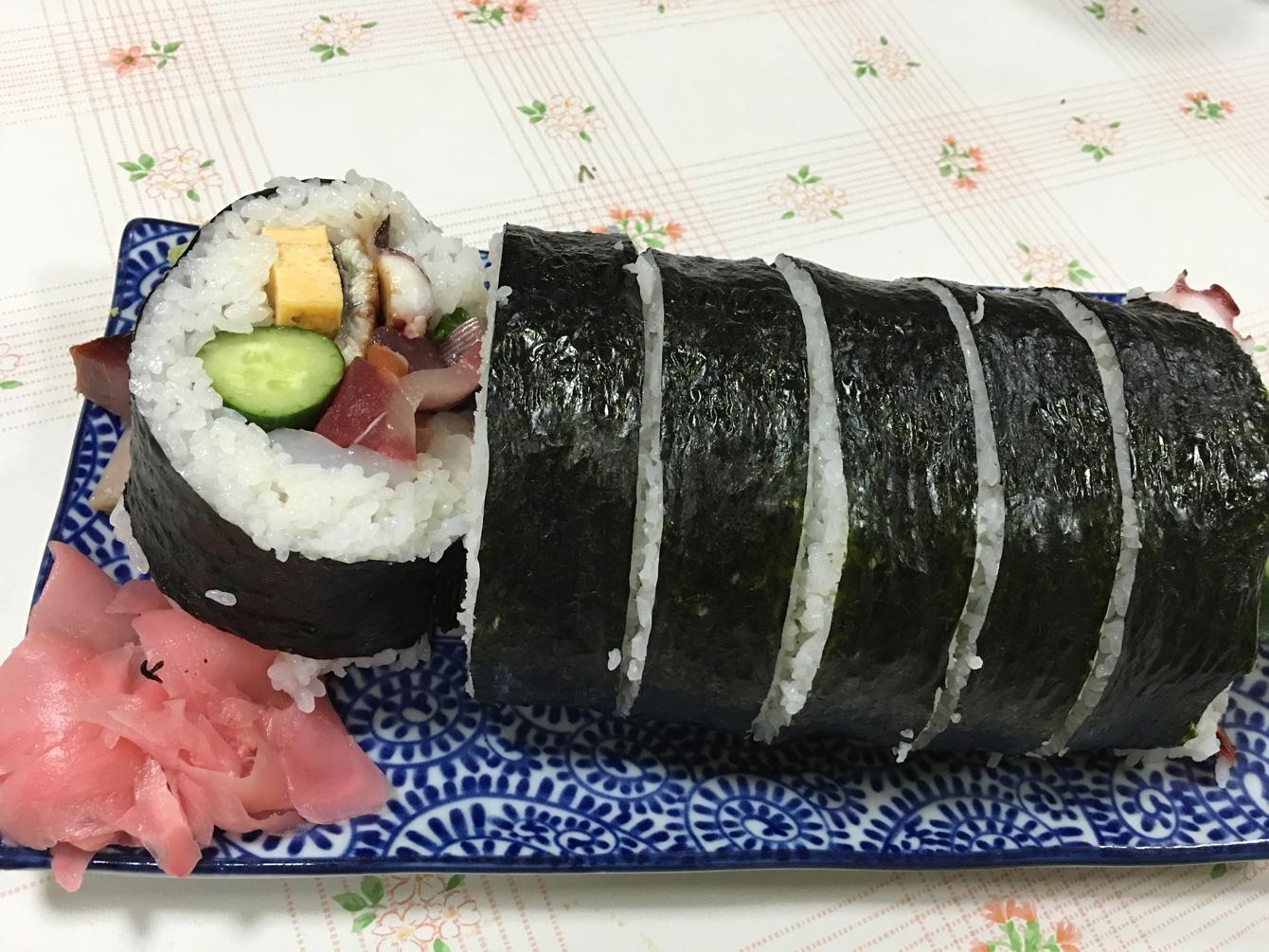 どーん!名物、一口では入りきらない手巻き寿司。海苔巻きに収まりきらない魚たちがいきいきと飛び出している。