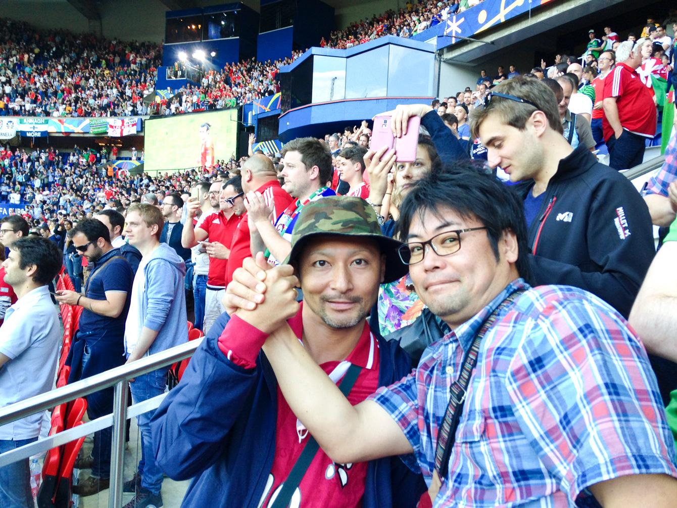 サッカースタジアムでのふたり。児島さん(左)と弊社代表・祁答院(右)