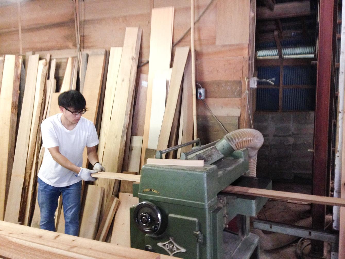 自動カンナ盤で木材の表面を削り取る。