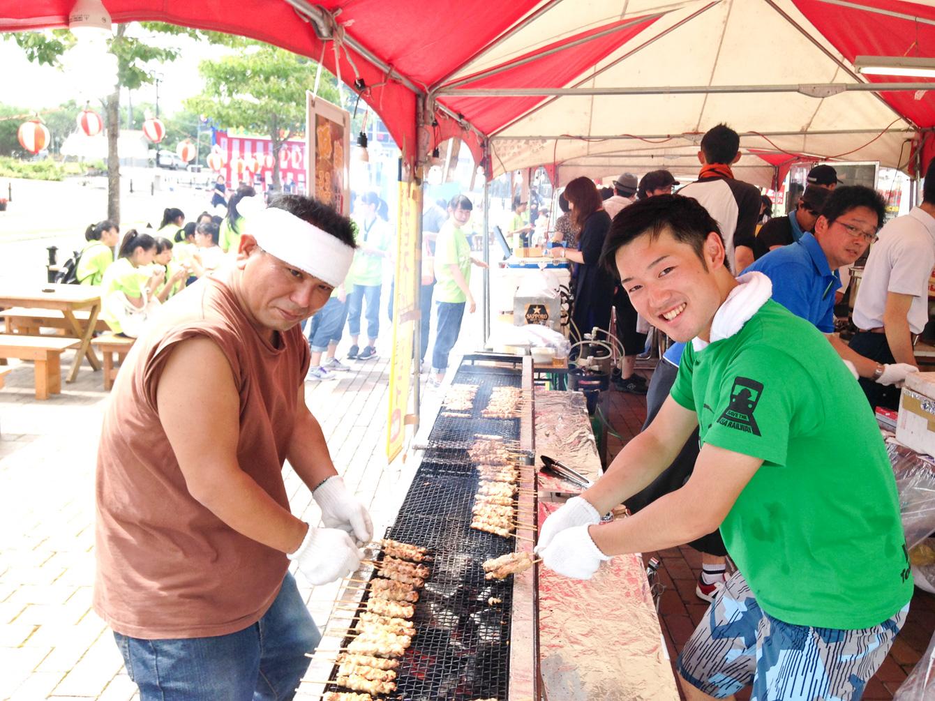 屋台で焼き鳥を焼いている様子。青年部の中山さん(左)と小松(右)。