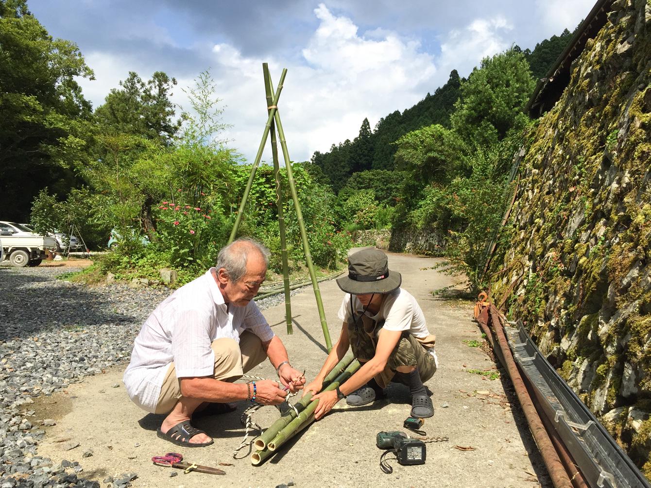 山姥オーナーの中山啓さん(左)に竹の組み立て方を教わる山田さん(右)。