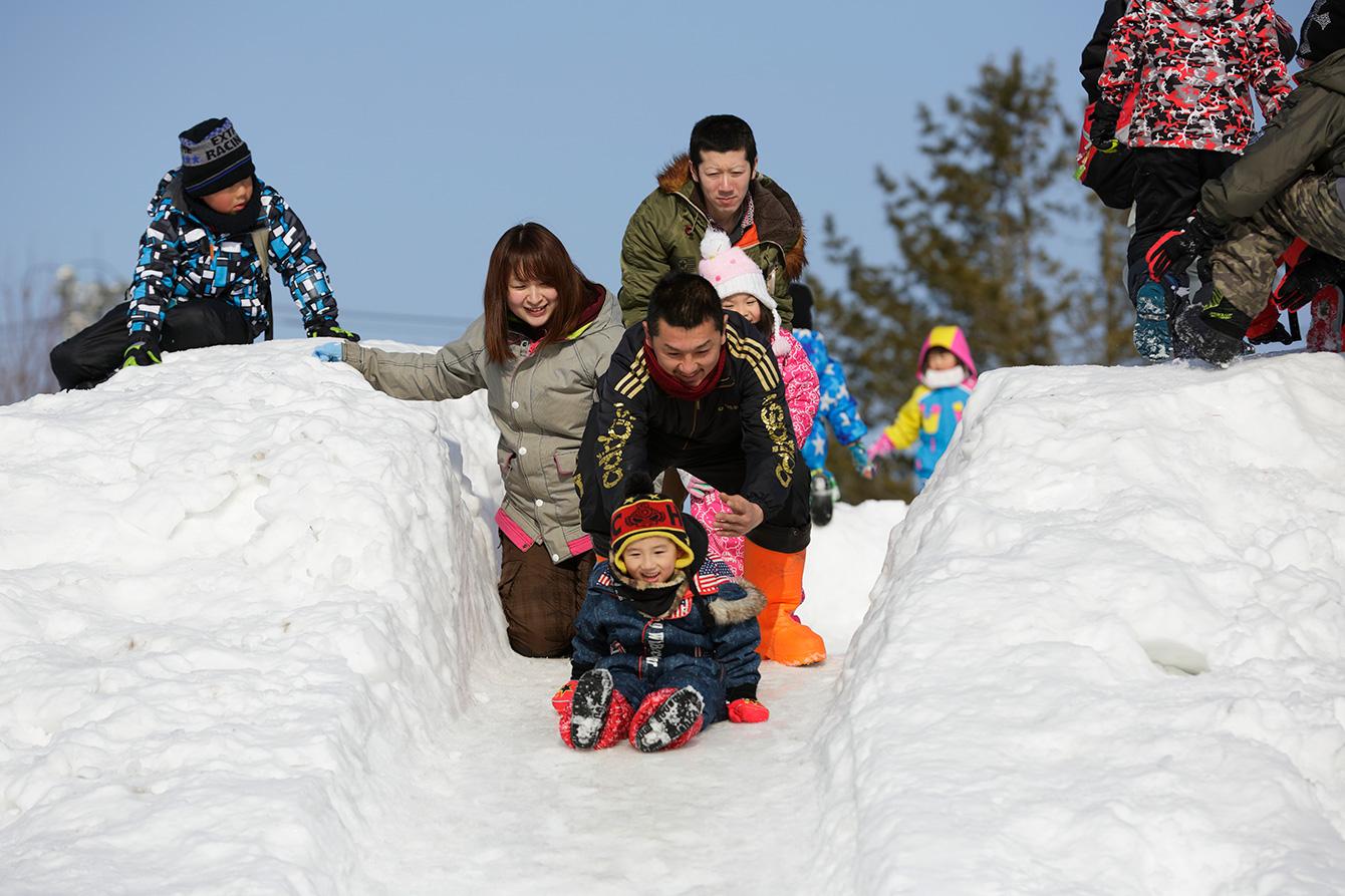 大きな滑り台で滑る子どもたち。