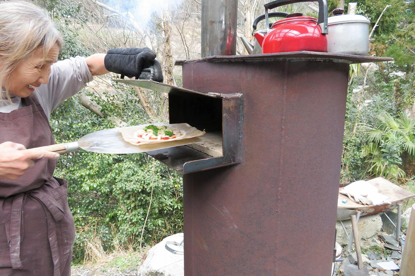 廃棄予定のドラム缶で作ったオーブンで中山さん手作りのピザを焼く。