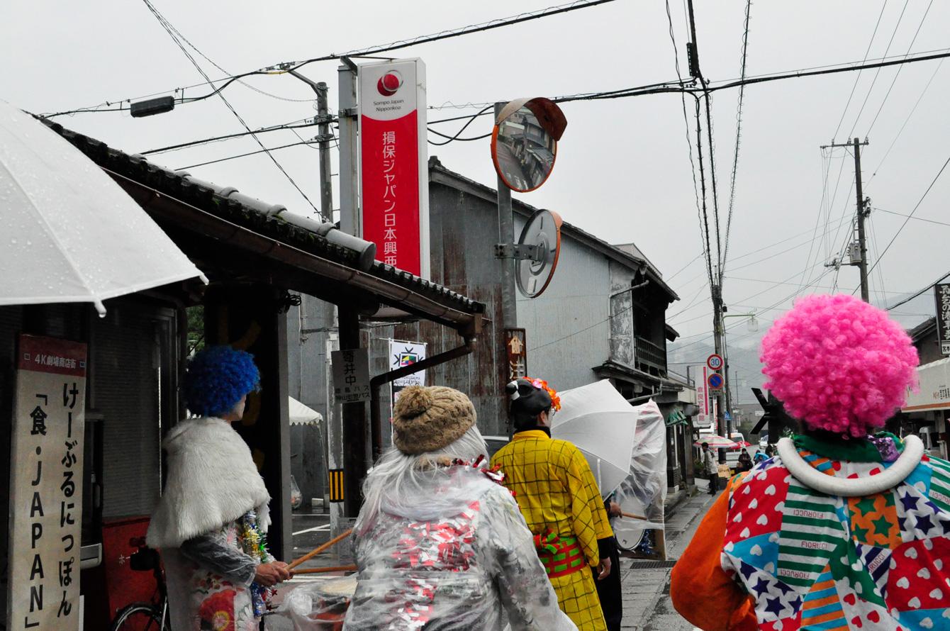 傘をさし、かっぱを着ながら商店街を練り歩く。